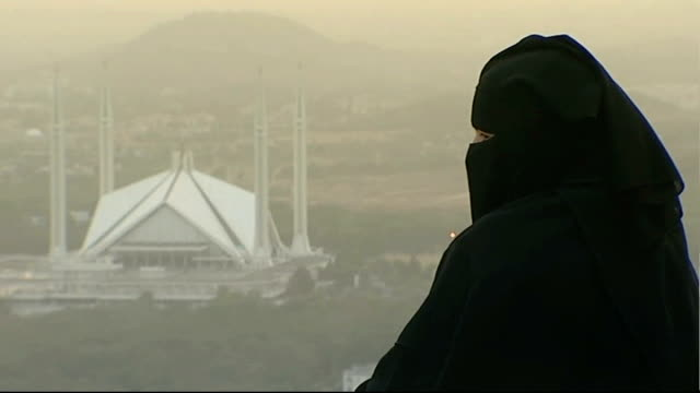 Islamabad Young Muslim woman in burka stands on hillside looking out at view mosque in distance