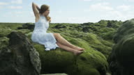 Woman in dress lays on moss covered rock