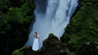 Woman in dress standing above waterfall in Iceland