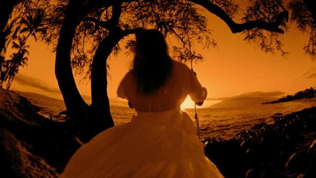 SEPIA FISHEYE REAR VIEW woman in dress swinging on tree swing / ocean in background  / Hawaii