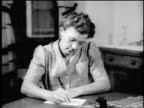B/W 1943/44 woman in eyeglasses writing letter at table / newsreel
