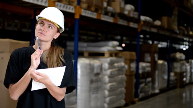 Woman in factory thinks, writes and smiles