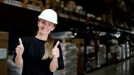 Frau in Fabrik mit Daumen hoch