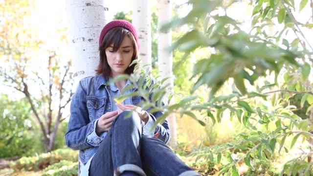 woman in fall aspen trees writing in diary