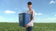 Woman in field with recycling bin full of plastic bottles