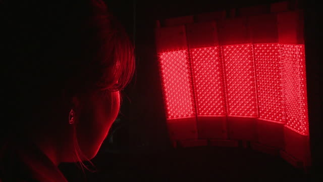 A woman in front of infrared light therapeutic apparatus for skin