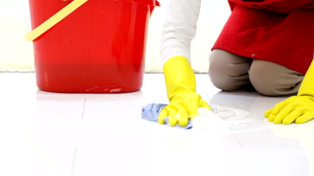 Woman in gloves cleaning a floors.