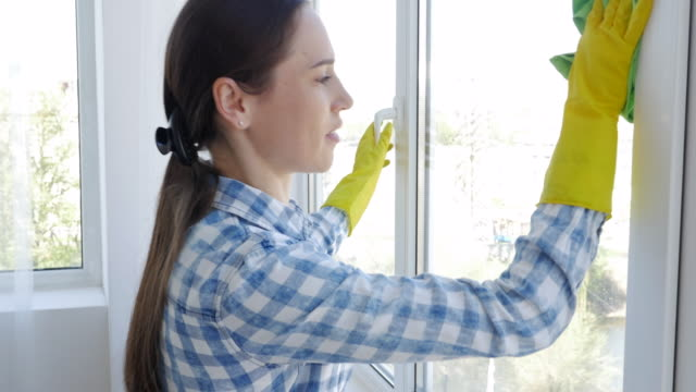 Woman in gloves cleaning window with rag and cleanser spray at home