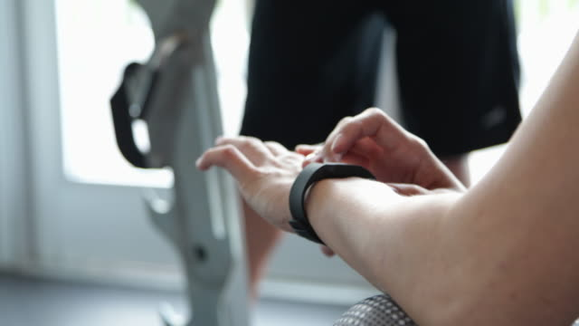 CU  Woman in gym setting fitness tracking device.