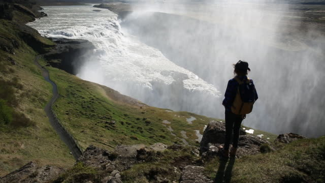 Woman in hat stands on cliff overlooking waterfall in Iceland