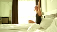 Woman in hotel room, arms outstretched