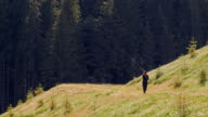 Woman in long black jacket walking alone in mountains