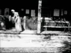 Woman in long dress sweeping porch of wooden home w/ period broom WS Woman in long dress walking into simple wooden home w/ no porch narrow windows