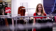 Woman in red dress chooses trousers in clothing store