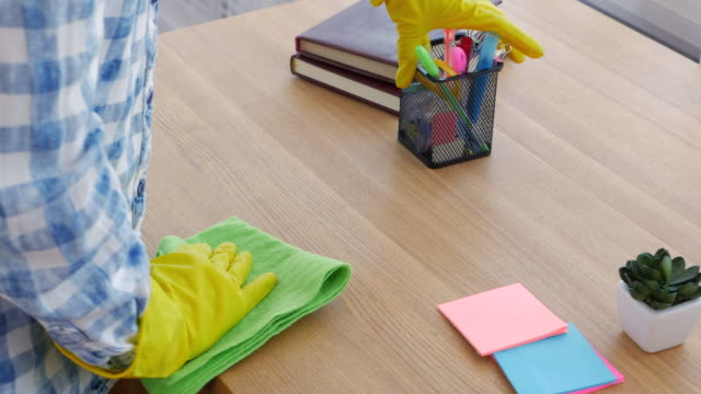Woman in rubber gloves cleaning the desk