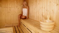 Woman in sauna splashes out the water to get steam