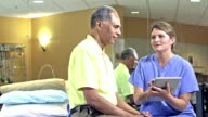 Woman in scrubs with digital tablet talks to patient
