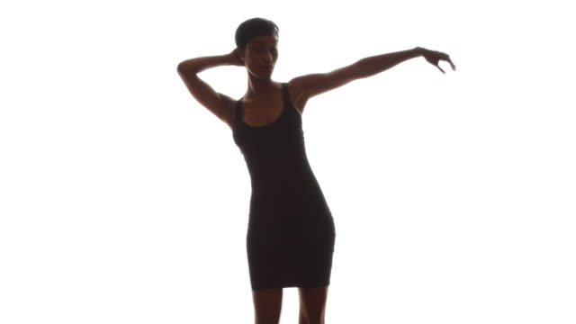 Woman in skin tight black dress dancing in slow motion