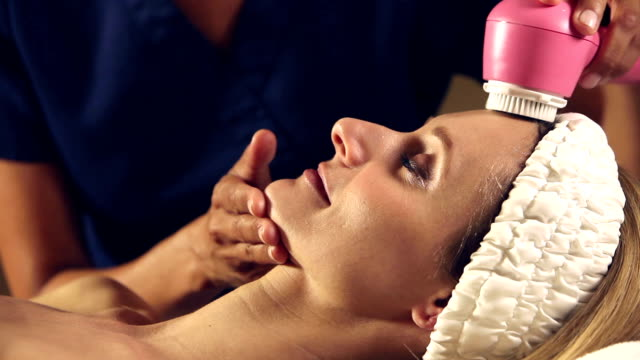 Woman in spa getting facial massage