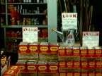 1965 MS Woman in store walking by product display of cans of Triox pesticide/ Sign with text saying Look over watering can/ Woman stopping to look