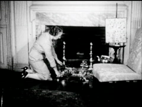 Woman in suit by fireplace demonstrating antique Box Iron w/ insert placing heated metal w/ tongs into hollow center placing iron onto metal holder...