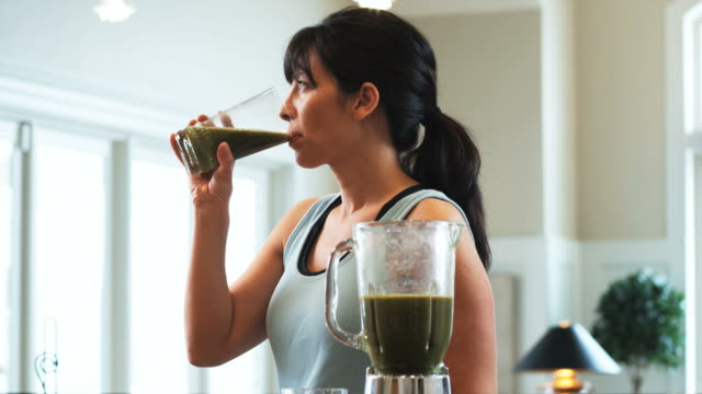 woman in the kitchen drinking a fruit smoothie