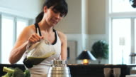 woman in the kitchen making a green smoothie in the blender and pouring a glass for her husband