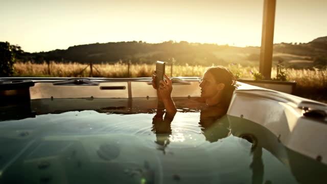 Donna in bagno termale con digital tablet