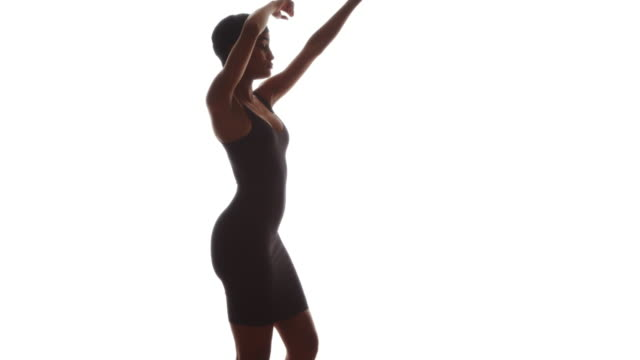 Woman in tight black dress dancing on white background