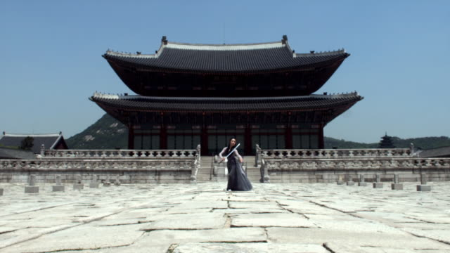 WS Woman in traditional dress performing a sword dance behind Gyeongbokgung Palace / Seoul, South Korea