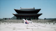 WS ZO Woman in traditional dress performing Buddhist Dance behind Gyeongbokgung Palace / Seoul, South Korea