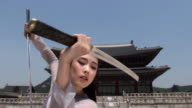 CU Woman in traditional dress performing sword dance behind Gyeongbokgung Palace / Seoul, South Korea
