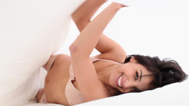 MS Woman in underwear lying under bed sheet, smiling / Brussels, Brabant, Belgium