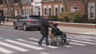 Woman in wheelchair being pushed across the street in Greenwich Village