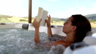 Woman in whirlpool jacuzzi reading a book