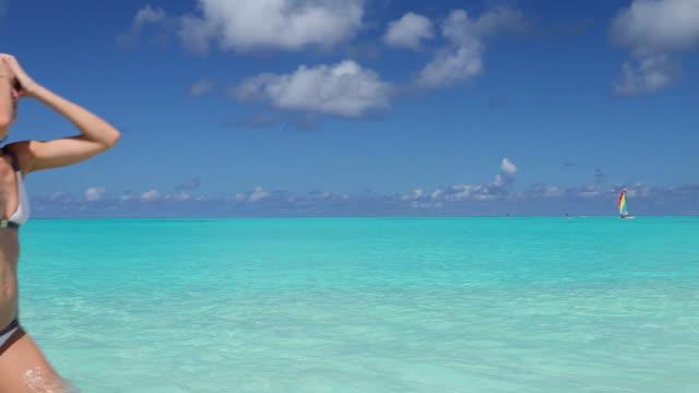Woman in white Bikini walking through blue Lagoon