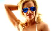 Woman in white bikini with sunglasses dancing.