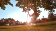 SLO MO Woman in white dress swinging towards the sun