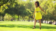 woman in yellow dress dancing in a park