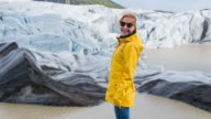 Woman in yellow raincoat standing at the bottom of Icelandic glacier