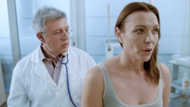 Woman inhaling and exhaling while doctor is auscultating her lungs
