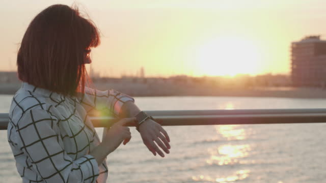 Woman interacts with a smart watch during sunset