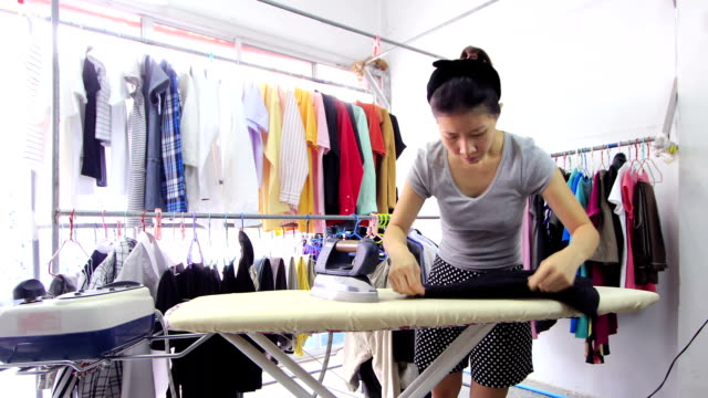 Woman ironing with steam iron at home, time lapse