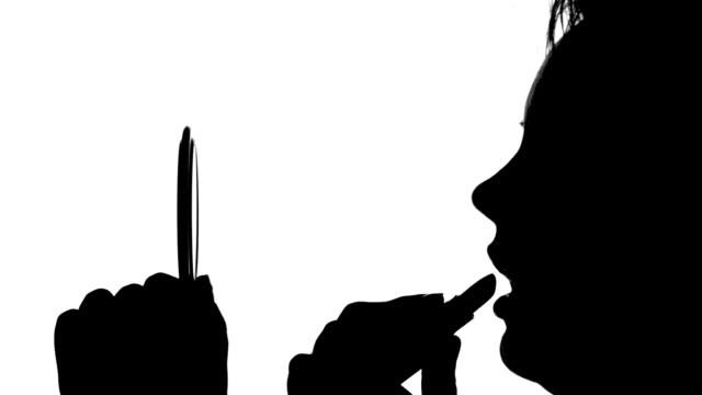 Woman is applying lipstick