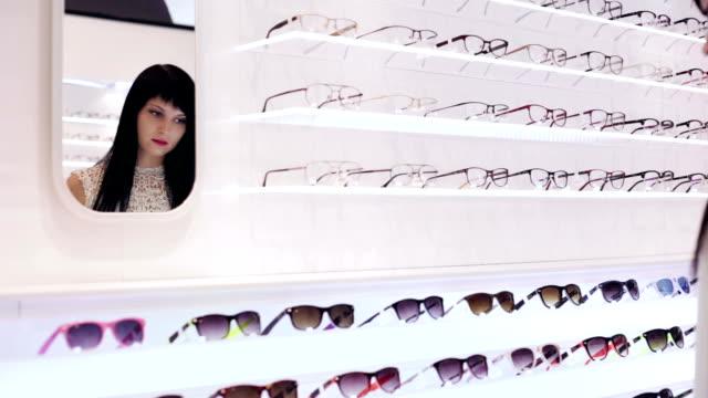 Woman is choosing a pair of sunglasses in optic shop