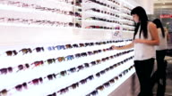Woman is choosing a pair of sunglasses in optic shop
