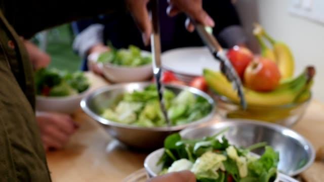 Vrouw is vullen salade kommen en ze overhandigen aan de gasten op diner
