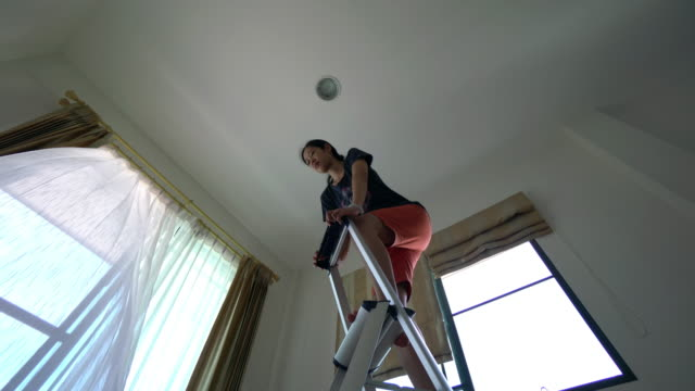 Woman is installing light in the house