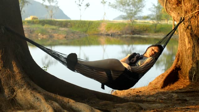 Woman is relaxing in beach hammock