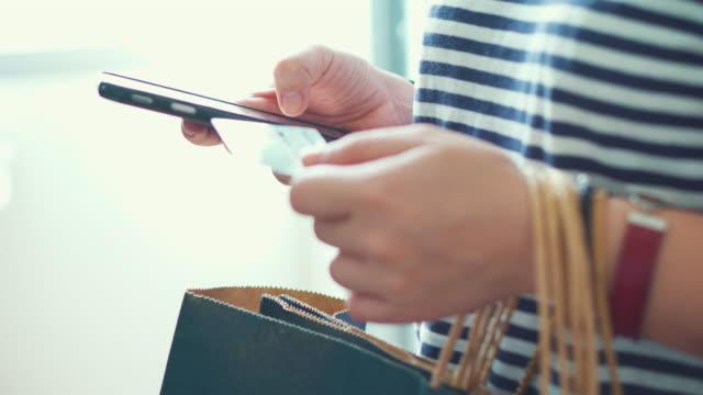 Kvinnan shopping online med hjälp av en smartphone, nära-up